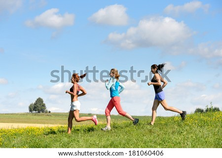 Female friends running downhill through sunny meadow summer sport - stock photo