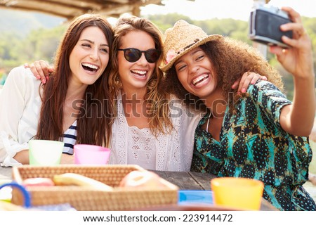 Female Friends Taking Selfie During Lunch Outdoors - stock photo
