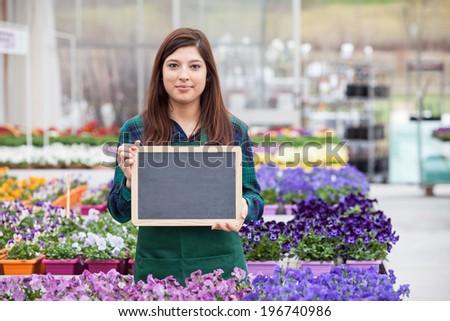 Female Garden Worker Holding an blank chalkboard - stock photo