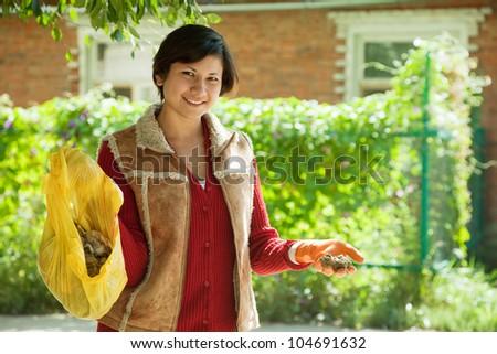 Female gardener fertilizes the soil in garden - stock photo