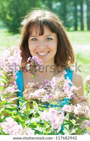 Female gardener in phlox plant at garden - stock photo
