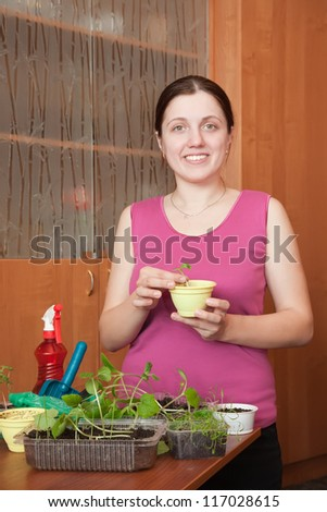 Female gardener with various seedlings at home
