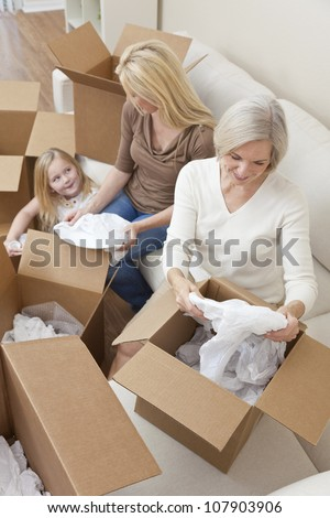 Female generations of a family, mother, daughter & grandmother unpacking boxes and moving into a new home. - stock photo