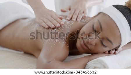 Female getting a salt scrub beauty treatment in the health spa - stock photo