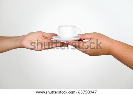 Female giving cup of coffee to another woman - stock photo