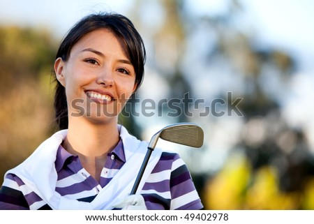 Female golf player outdoors with a club smiling - stock photo