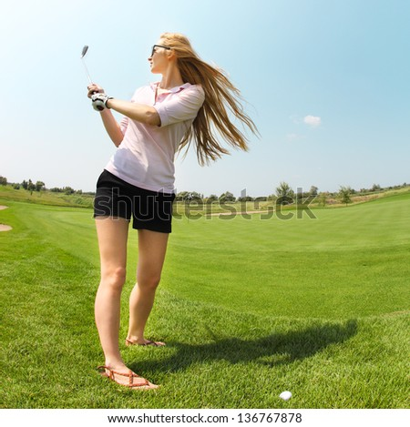 Female golf player practicing to hit the ball at the course