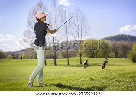 Female golf player swinging golf club. - stock photo