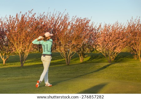 Female golf player teeing-off during dusk. - stock photo