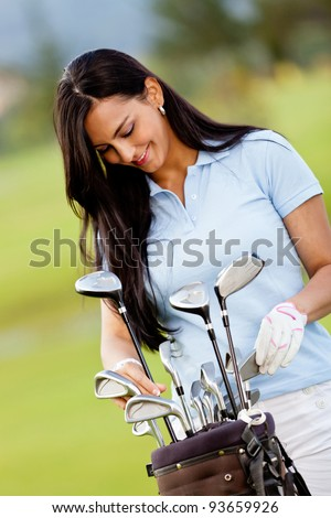 Female golf player with a bag at the course - stock photo