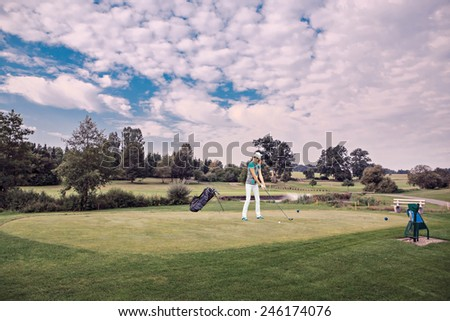 female golf player with a golf club on the course - stock photo