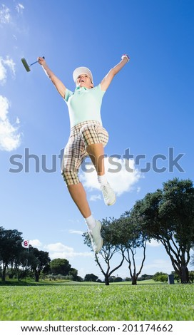 Female golfer leaping and cheering on a sunny day at the golf course
