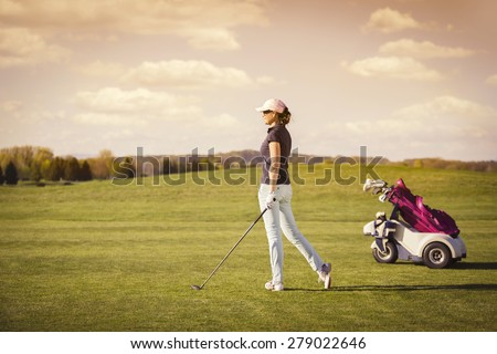 Female golfer on fairway with golf club and bag with empty copyspace. - stock photo