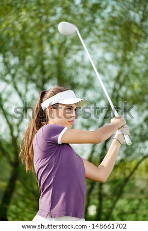 Female golfer shooting a golf ball