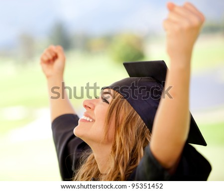 Female graduate with arms up succeeding in education