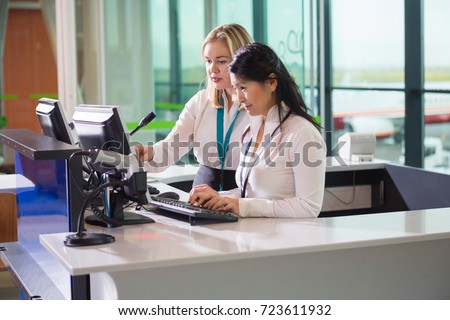 Female Ground Staff Using Computer At Counter In Airport