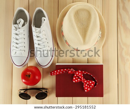 Female gumshoes with accessories on wooden background - stock photo