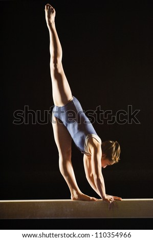 Female gymnast striking pose on balance beam - stock photo