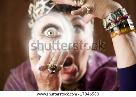Female gypsy fortune teller holding a crystal ball to her eye - stock photo