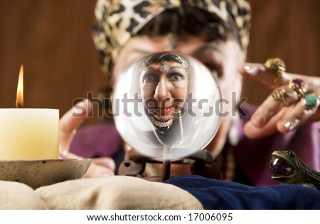 Female gypsy fortune teller looking into a crystal ball - stock photo