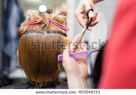 Female hair cutting scissors in beauty salon - stock photo