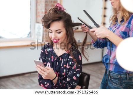 Female hairdresser applying hair straightener for long hair of smiling young woman using smartphone in dressing room - stock photo
