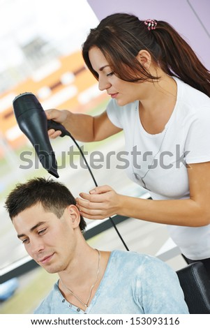 Female hairdresser drying hair with blow dryer of man client at beauty parlour - stock photo