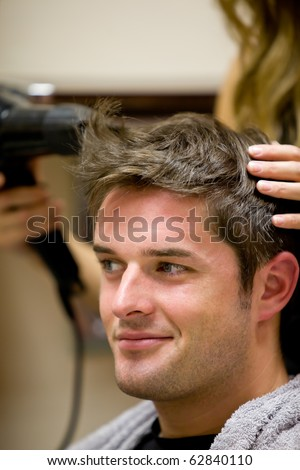 Female hairdresser drying her male customer's hair in her hairdressing salon - stock photo
