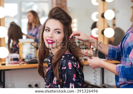 Female hairdresser standing and making hairstyle to cute lovely young woman in beauty salon - stock photo