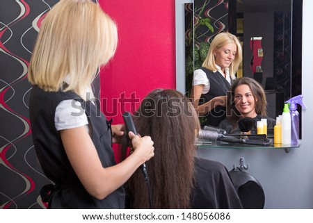 Female hairdresser straightening woman's hair with iron in beauty salon - stock photo