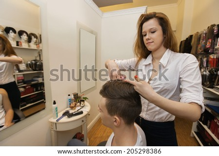 Female hairstylist cutting male customer's hair in shop