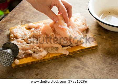 Female hand beat chicken fillet with hammer