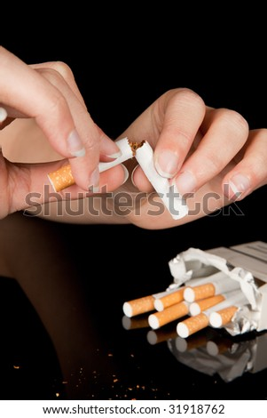 Female hand breaking a cigarette to stop smoking - stock photo