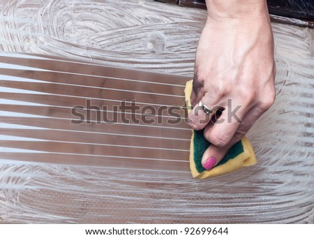 Female hand cleaning glass surface - stock photo