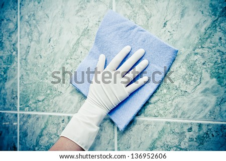 female hand cleaning kitchen tiles with sponge color processed - stock photo
