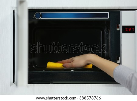 Female hand cleaning microwave with a sponge