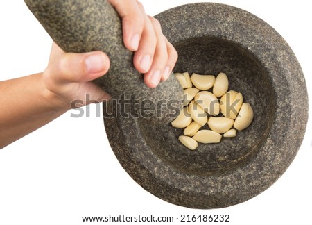 Female hand crushing garlics using stone pestle and mortar - stock photo