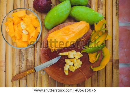 female hand cuts and makes the salad with mango papaya fruit banana passion fruit