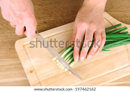 Female hand cutting chives on cutting board