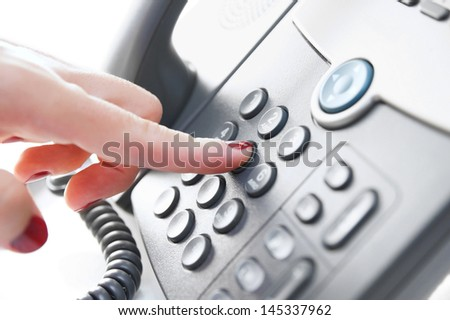 Female hand dialing a phone number - stock photo