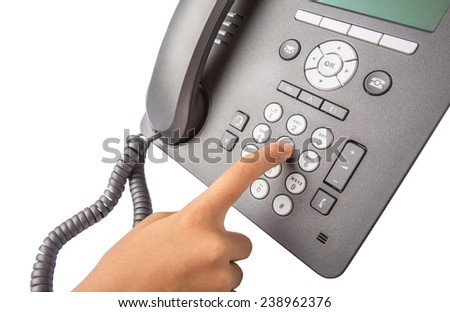 Female hand dialing numbers of desktop telephone  - stock photo