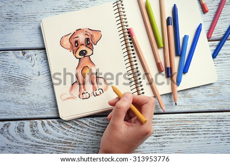 Female hand drawing dog in notebook on wooden table background - stock photo