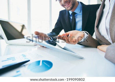 Female hand during explanation of electronic data in touchpad to her colleague - stock photo
