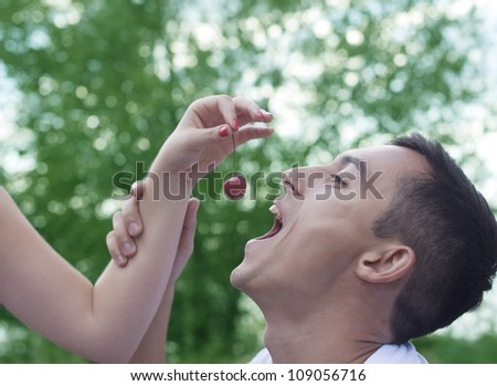 female hand feeds the beloved guy of ripe cherries