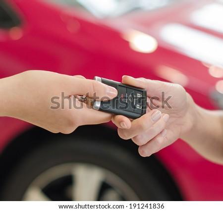 Female hand getting modern car key on red car background - stock photo