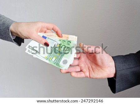 Female hand gives money, the man's hand takes them