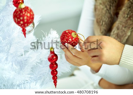 Female hand hanging a ball on a Christmas tree