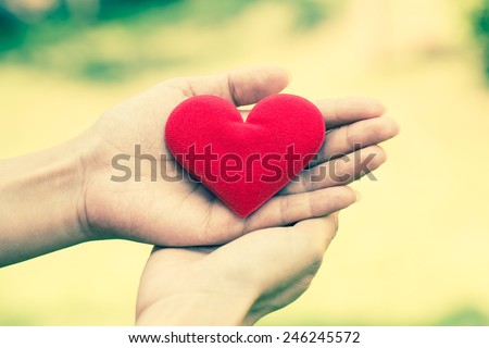 Female hand hold fabric red valentine heart with blur green leaf background. Retro filter.