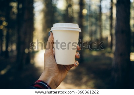 female hand holding a blank paper cup in a wooded landscape background - stock photo