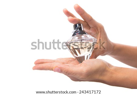Female hand holding a bottle of perfume over white background - stock photo